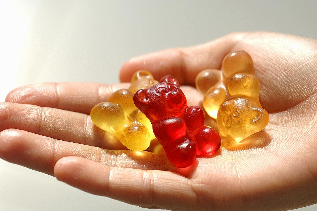 Three gummi bears in someone's hand
