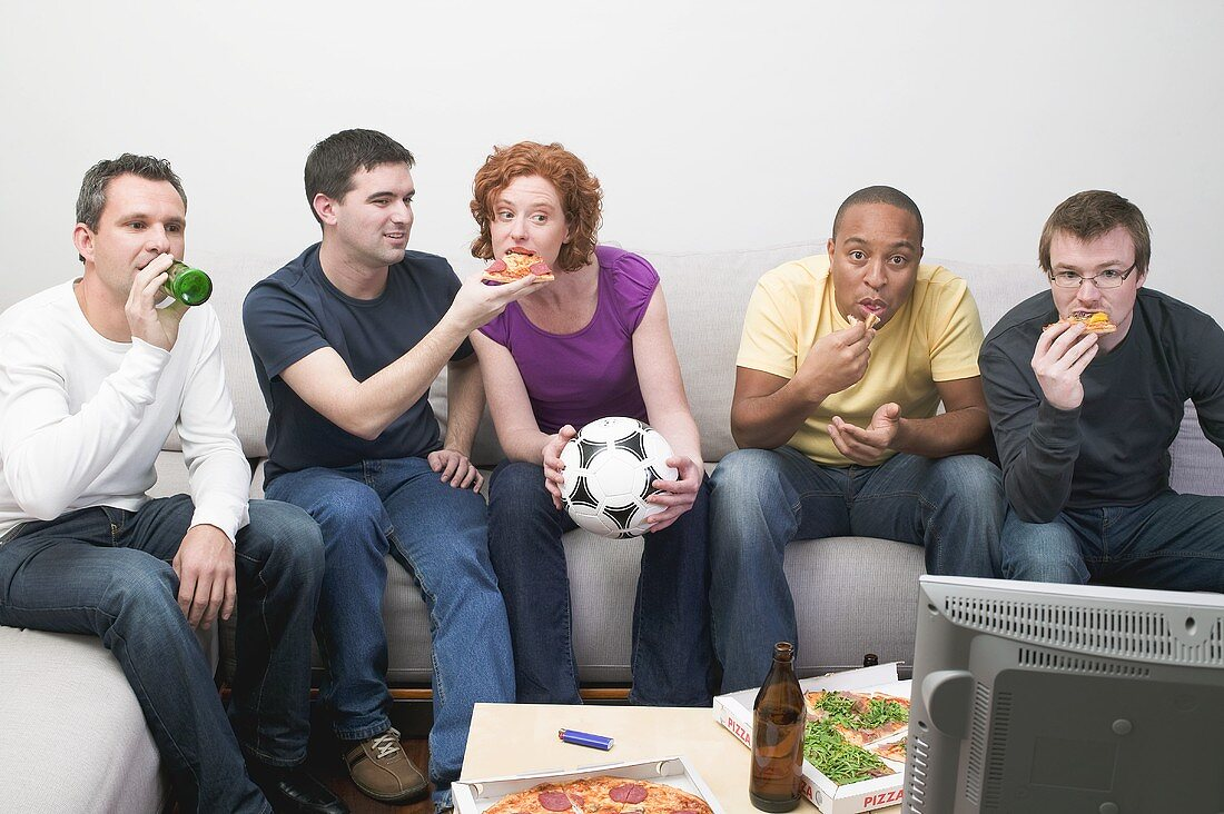 Friends sitting in front of TV with football, pizza & beer