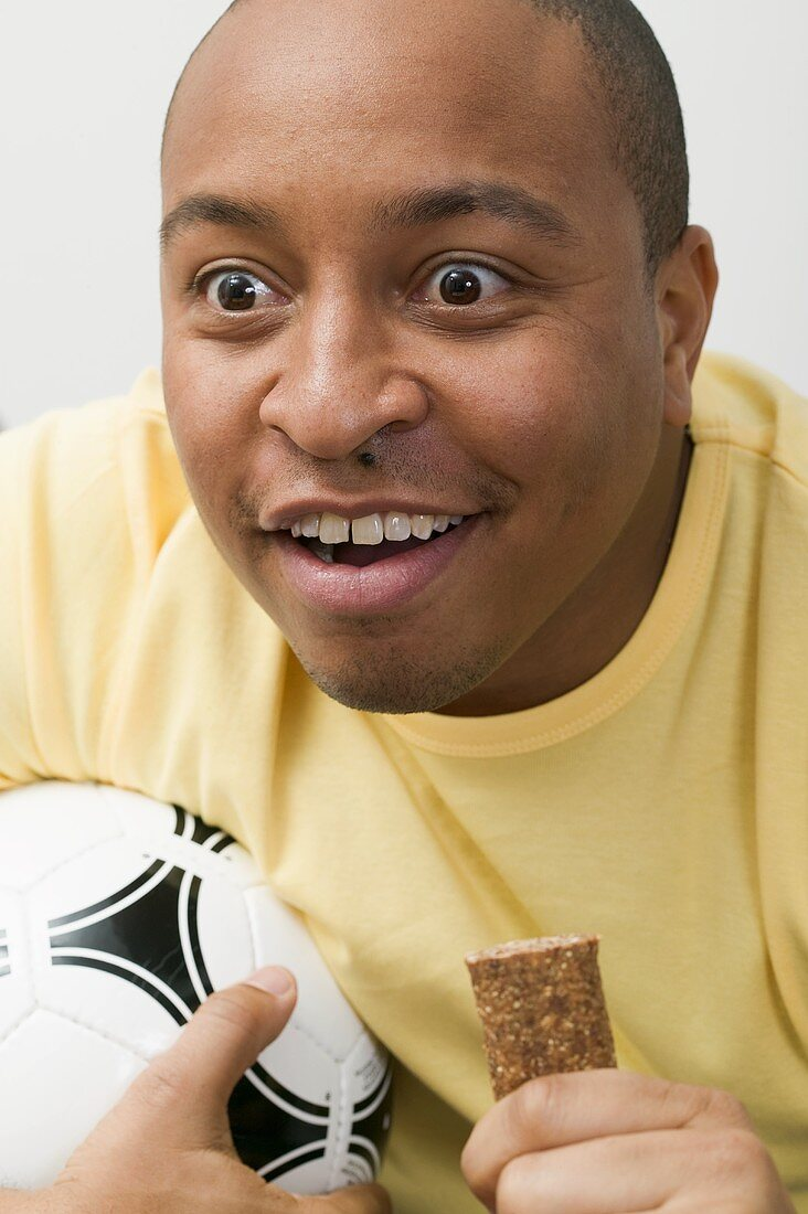 Young man with football and chocolate bar watching TV