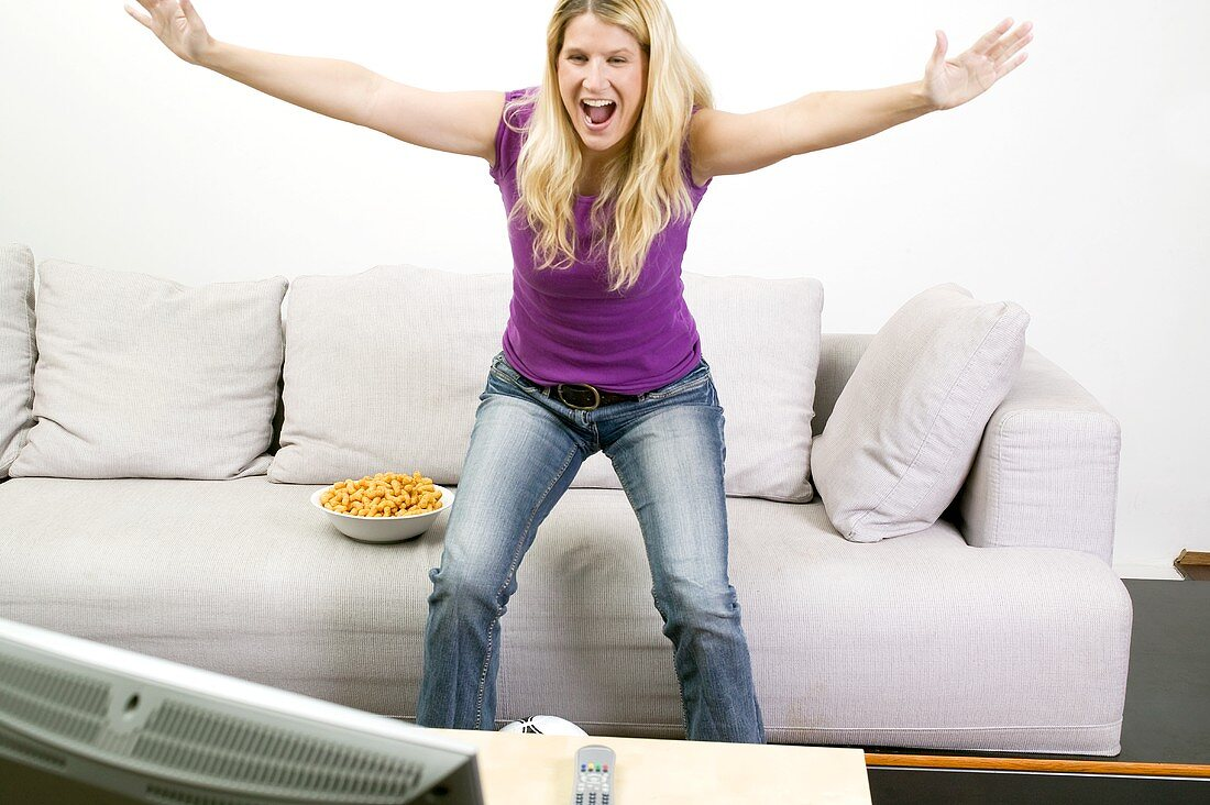 Young woman cheering in front of TV