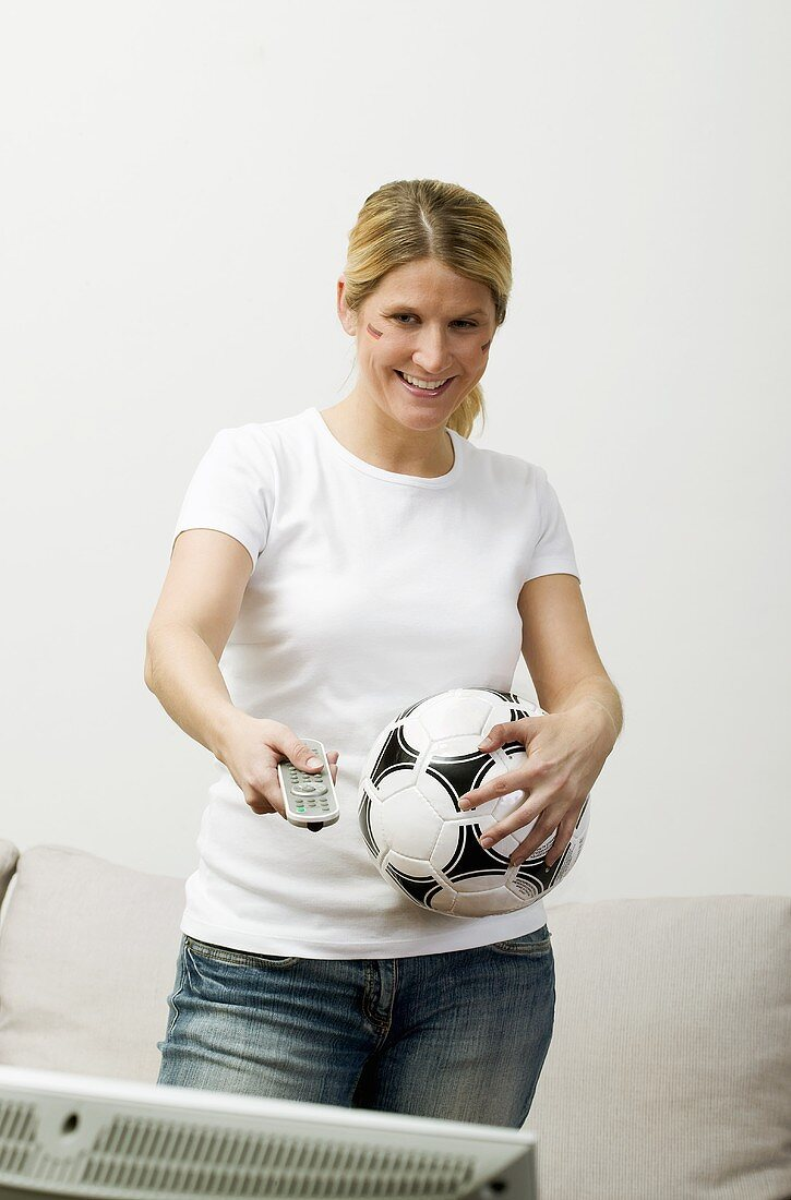 Young woman with football & remote standing in front of TV