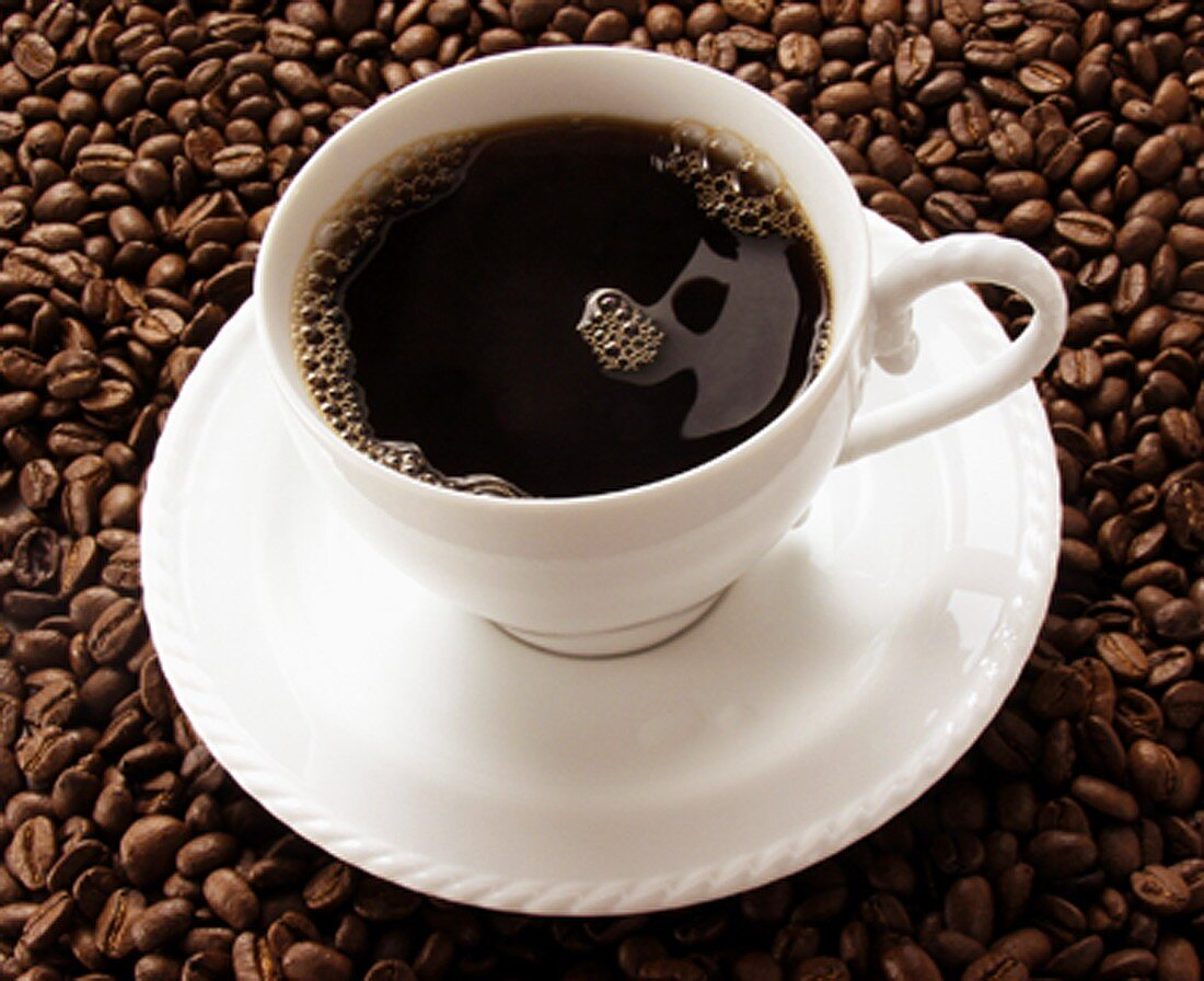 Cup of Black Coffee Resting on Coffee Beans