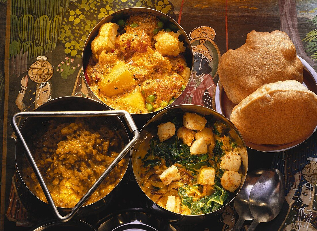 Spinach with diced cheese; potato curry; dal & puri