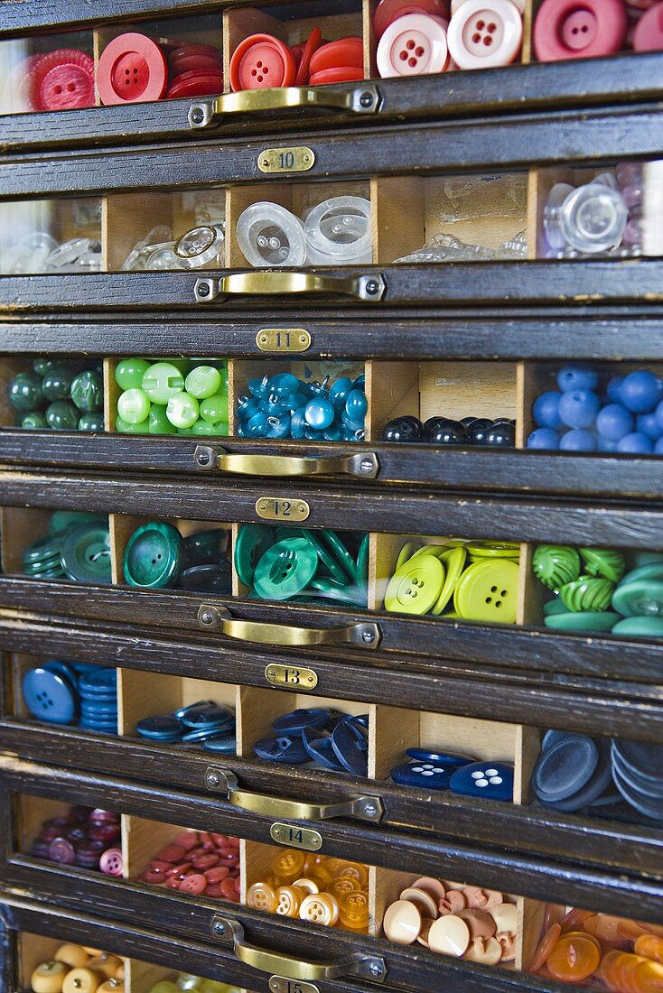 Various coloured buttons in compartments on a shelf