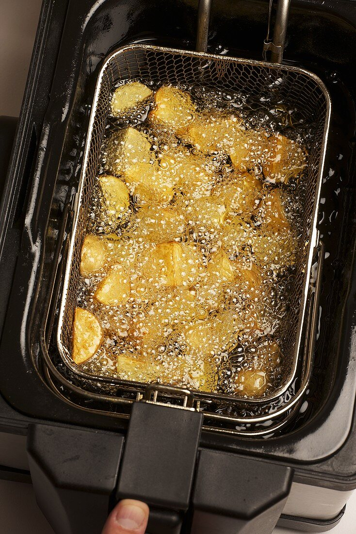 Potatoes being fried in a deep fat fryer