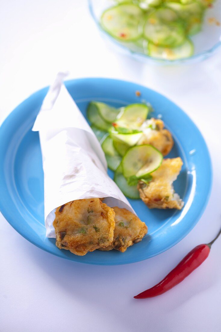 Fish cakes in a paper bag with a cucumber salad (Thailand)