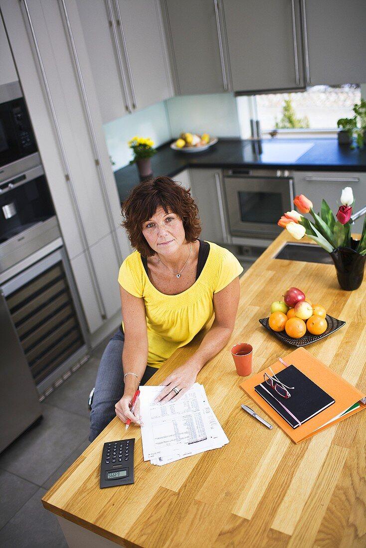 A woman checking bills at a kitchen table