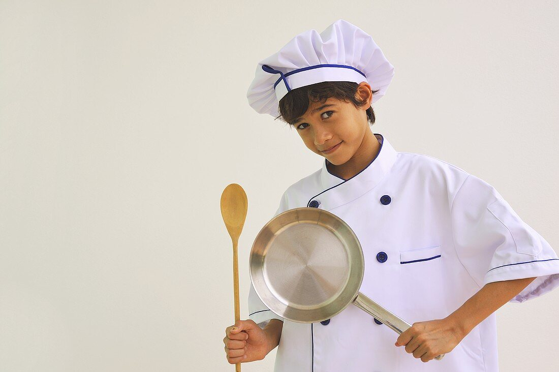 A boy dressed as a chef holding a pan and a wooden spoon