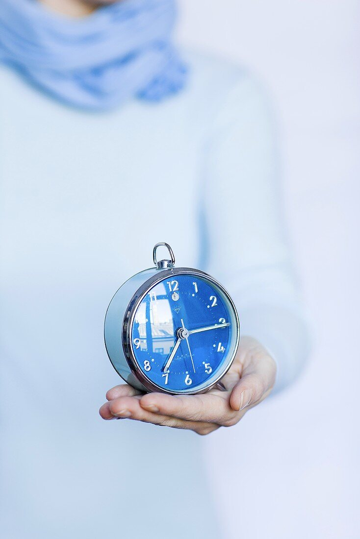 A woman holding an alarm clock