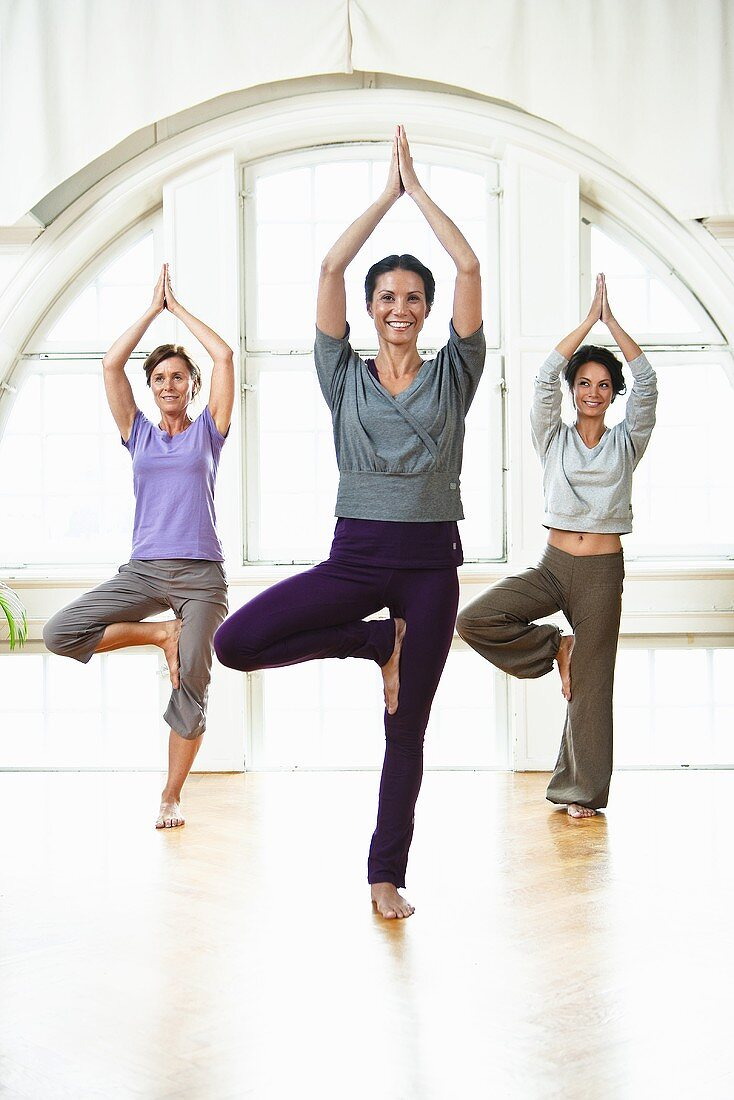 Three women practising yoga in a workout room