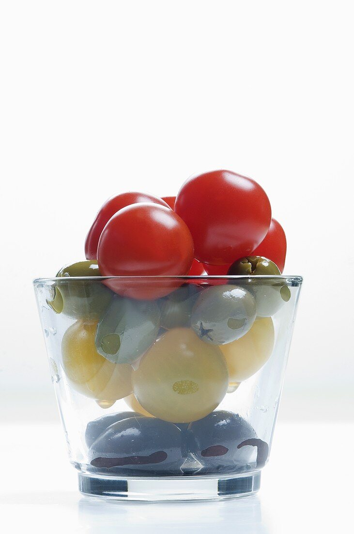 Cherry tomatoes and olives in a glass