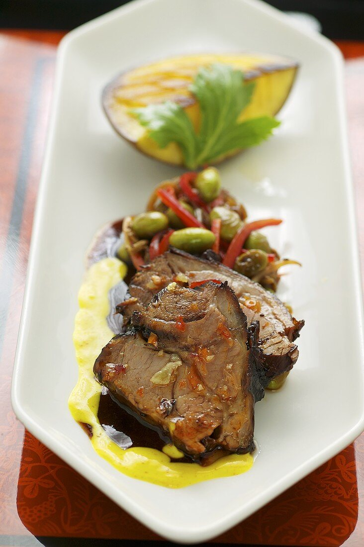 Braised lamb shoulder on turmeric sauce with vegetables and fried mango (Asia)