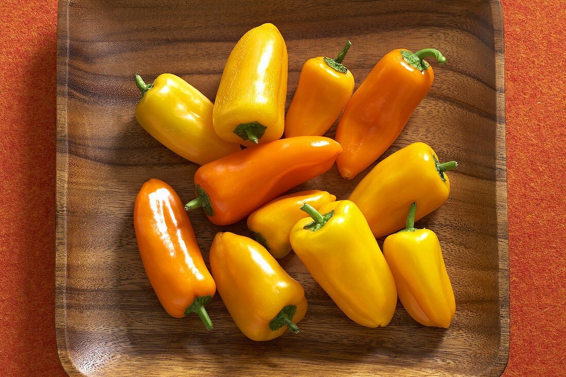 Yellow and orange mini peppers in a wooden crate