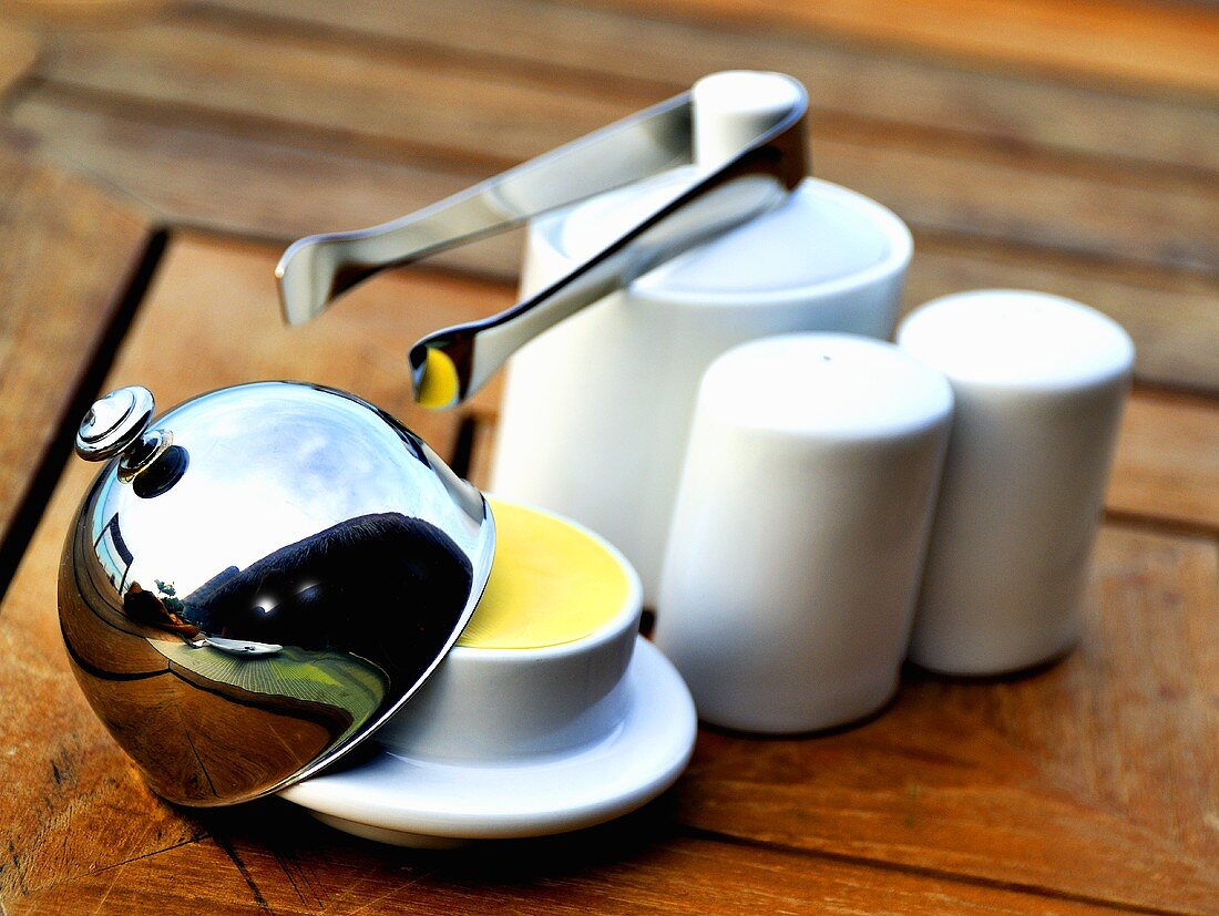 A butter cloche, salt and pepper shakers and a sugar pot