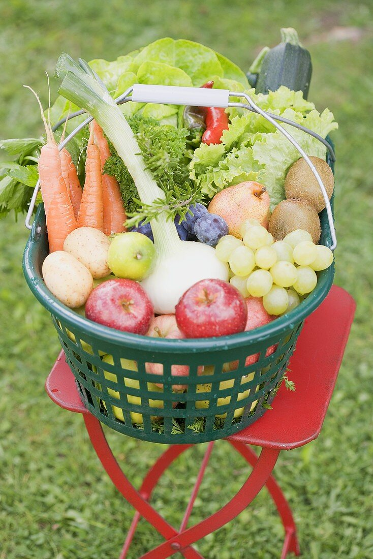 A basket of fresh fruit and vegetables on a garden table