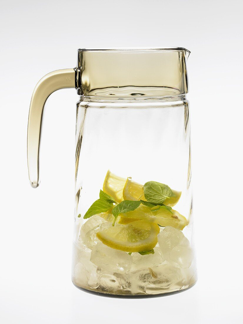 Glass carafe with lemons, mint and ice cubes