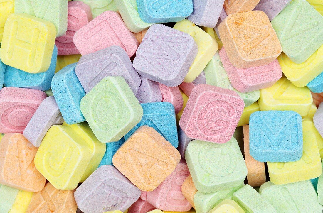 Brightly colored 'Pop Rocks' with letters stamped on top