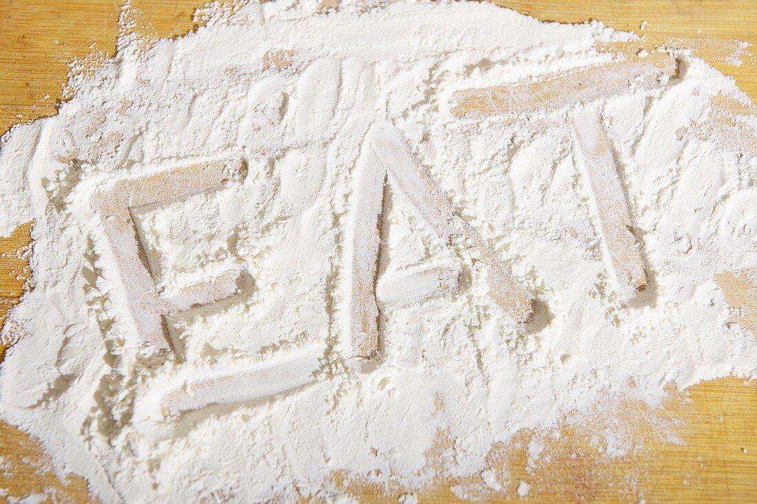 The word 'eat' written in flour