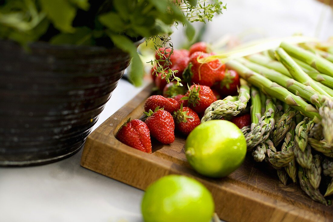 Strawberries, green asparagus and limes on a wooden board