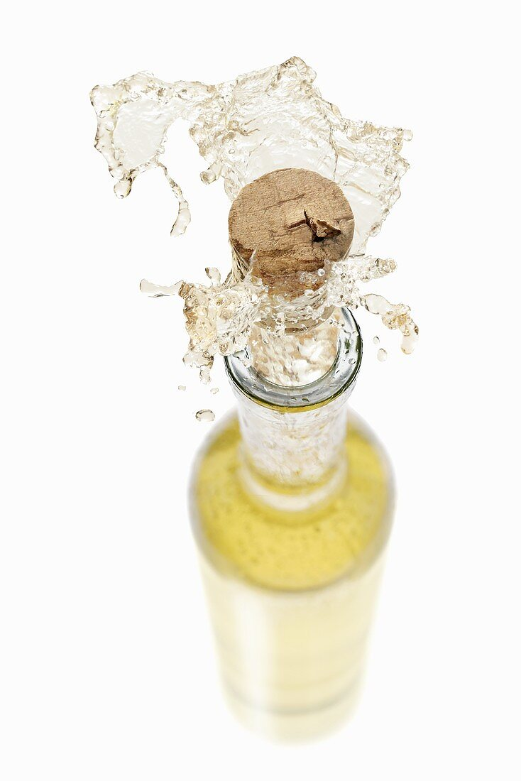 White wine spraying out of a bottle