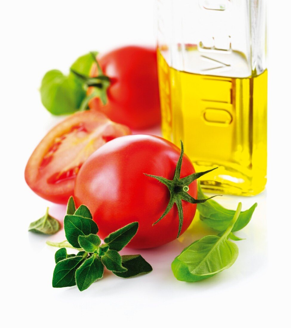 Tomatoes, a bottle of olive oil and fresh herbs (close-up)