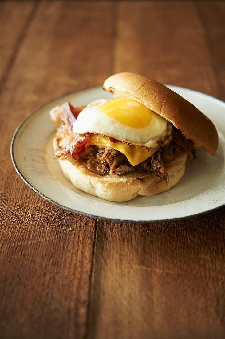 Barbecue Pulled Pork Sandwich with Bacon, American Cheese and a Fried Egg