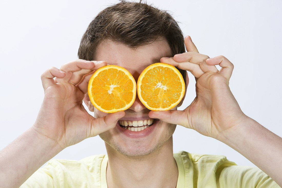 A young man holding orange slices in front of his eyes