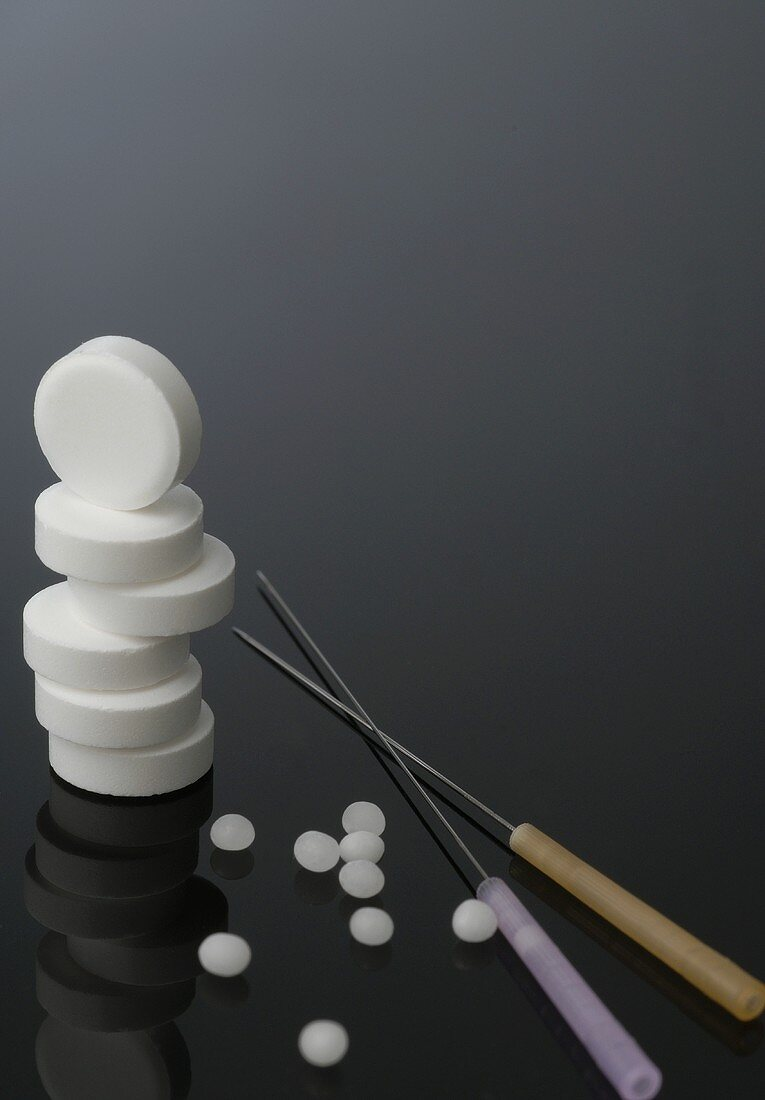 Stacked tablets, globuli (small pellets) & acupuncture needles