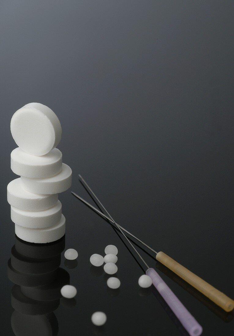 Tabletten, gestapelt, Globuli und Akupunkturnadeln