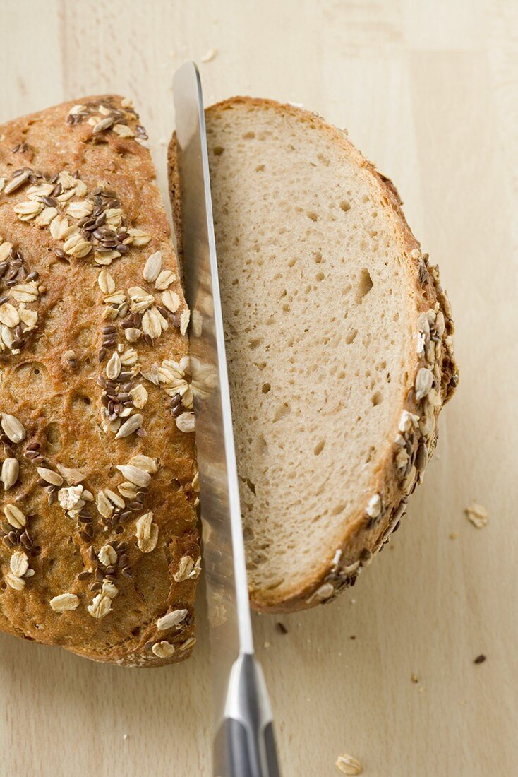 Halving a loaf of bread with a knife