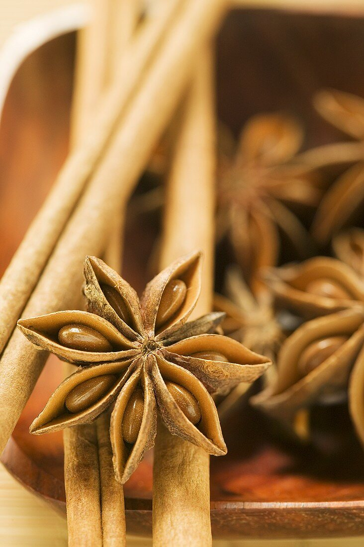 Star anise and cinnamon sticks in wooden bowl