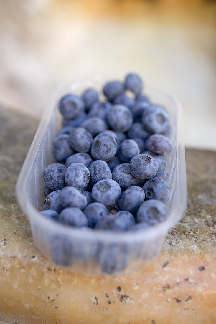 Blueberries in plastic punnet on a stone sink