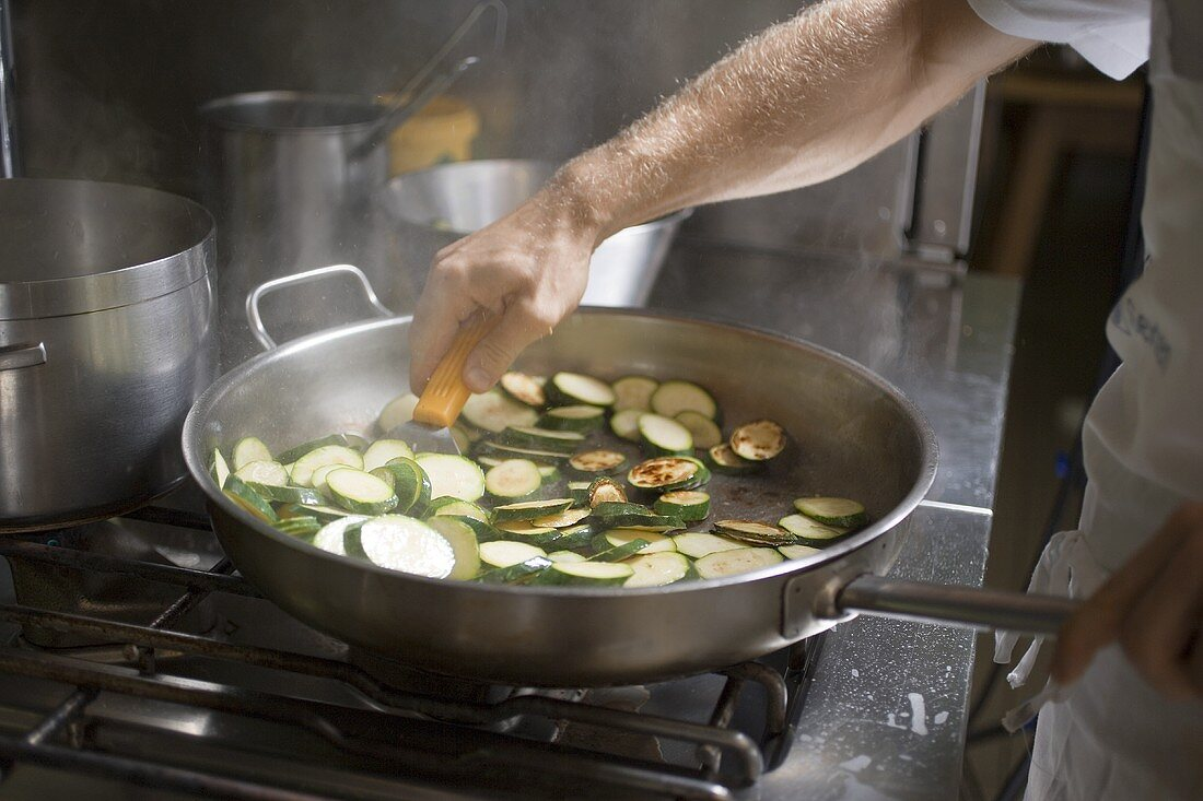 Turning courgette slices in frying pan