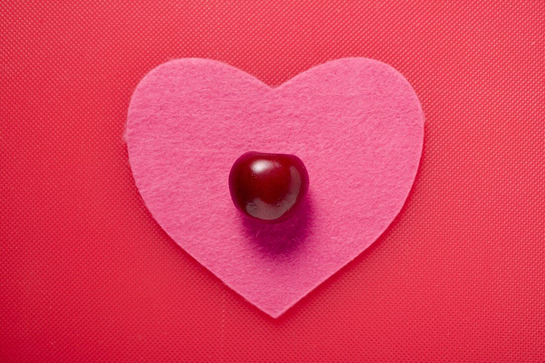 A cherry on a pink fabric heart