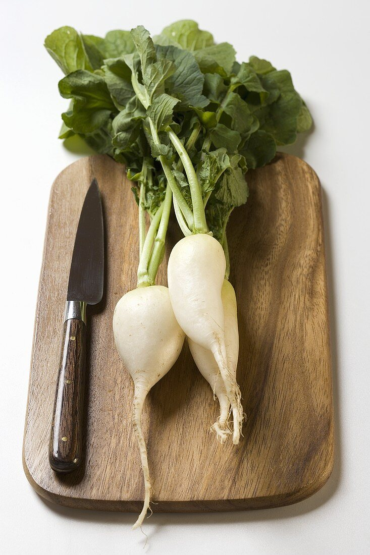 Icicle radishes with leaves & knife on chopping board
