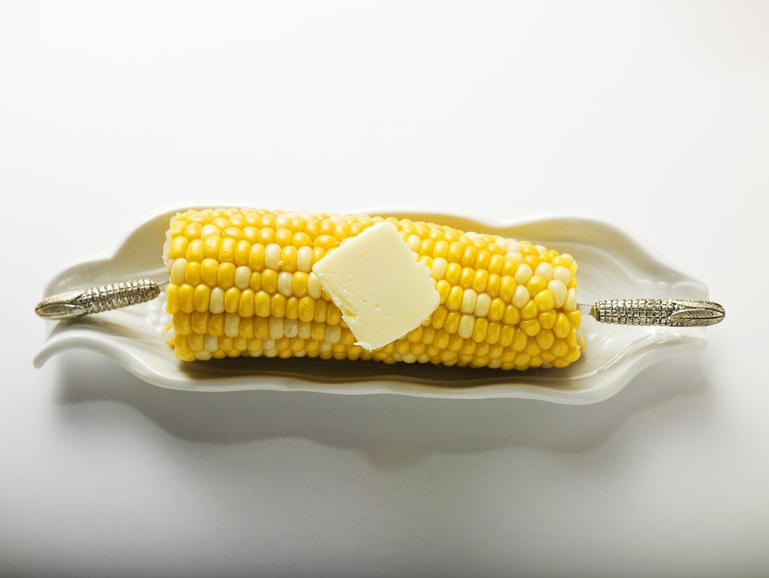Corn on the cob with knob of butter in white dish