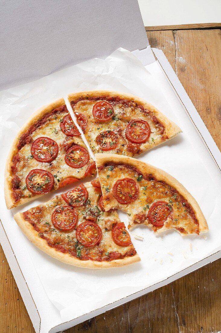 Cheese & tomato pizza with oregano (quartered) in pizza box
