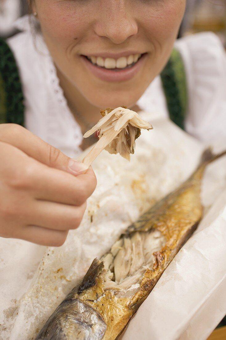 Woman eating Steckerlfisch (fish on stick, Oktoberfest, Munich)