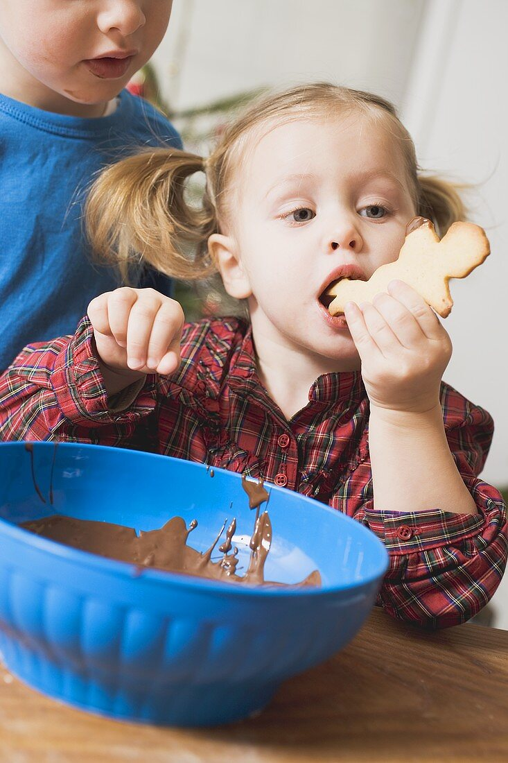 Girl eating Christmas biscuit with chocolate icing