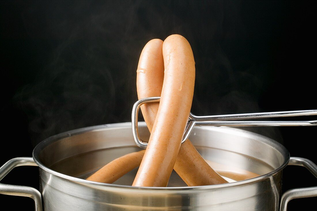 Lifting frankfurters out of hot water with tongs