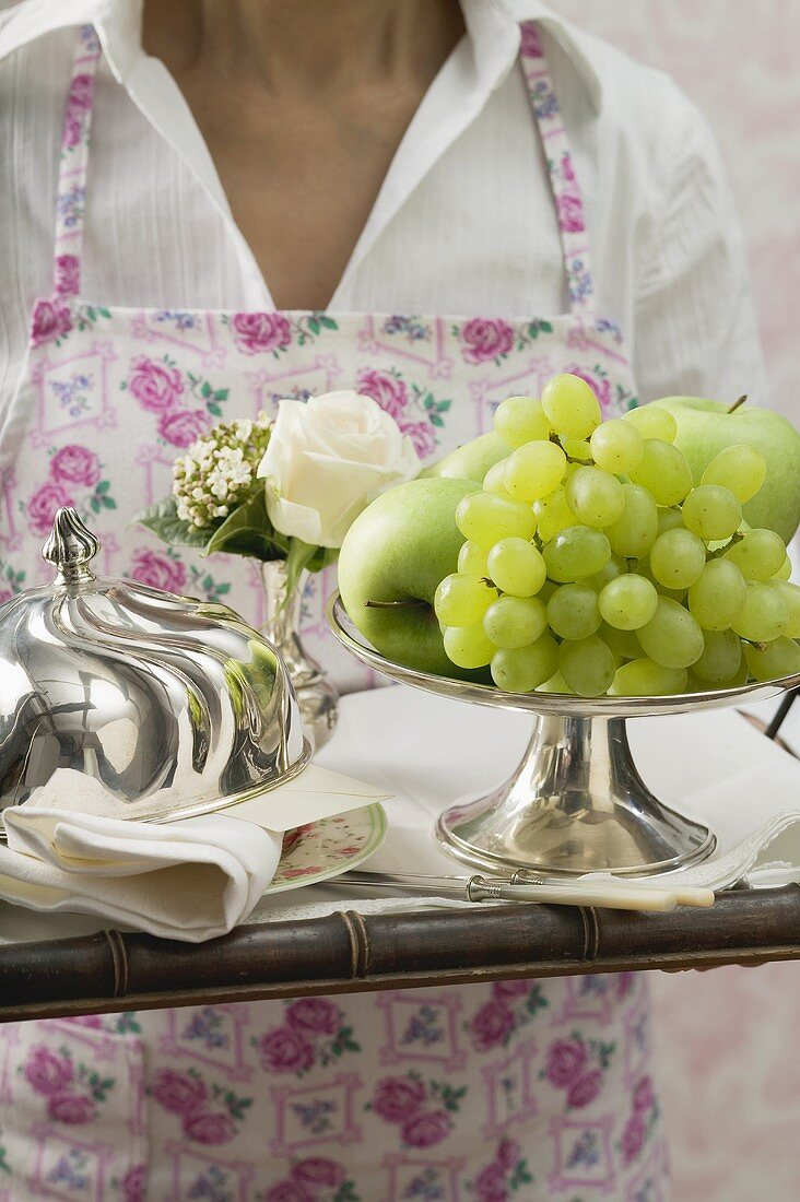 Chambermaid serving breakfast tray with fresh fruit