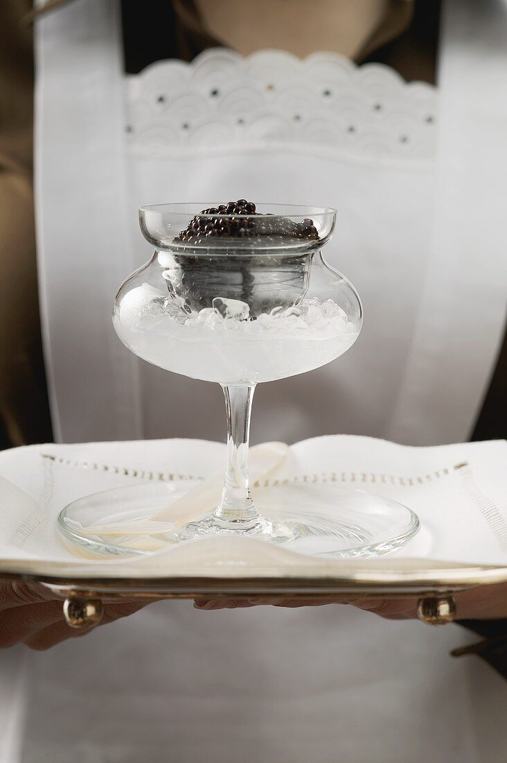 Chambermaid serving caviar in stemmed glass on tray