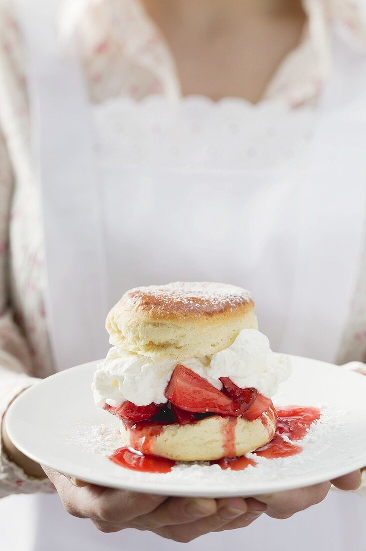Chambermaid serving strawberry shortcake on plate