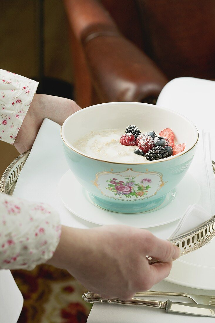 Hands serving bowl of porridge on a tray