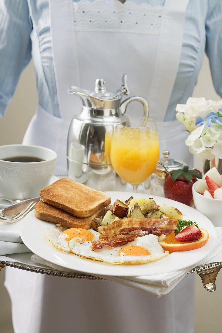 Chambermaid serving breakfast tray