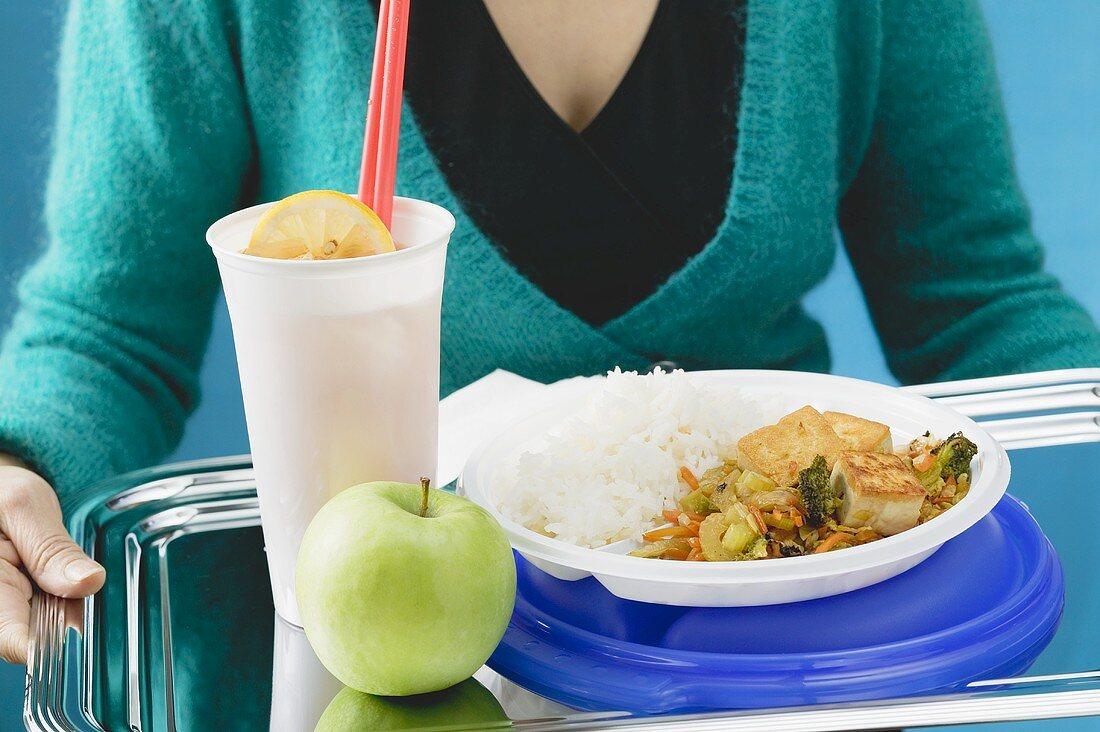 Fried tofu with stir-fried vegetables, apple & lemonade on tray