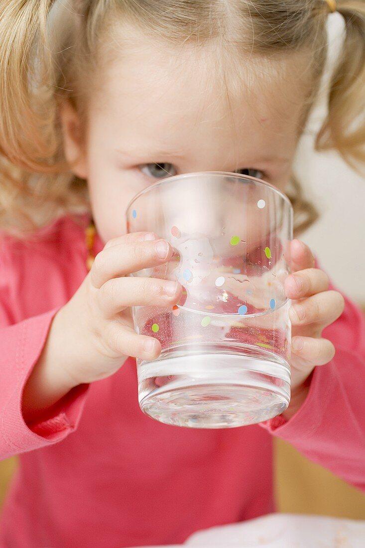 Small girl drinking a glass of water