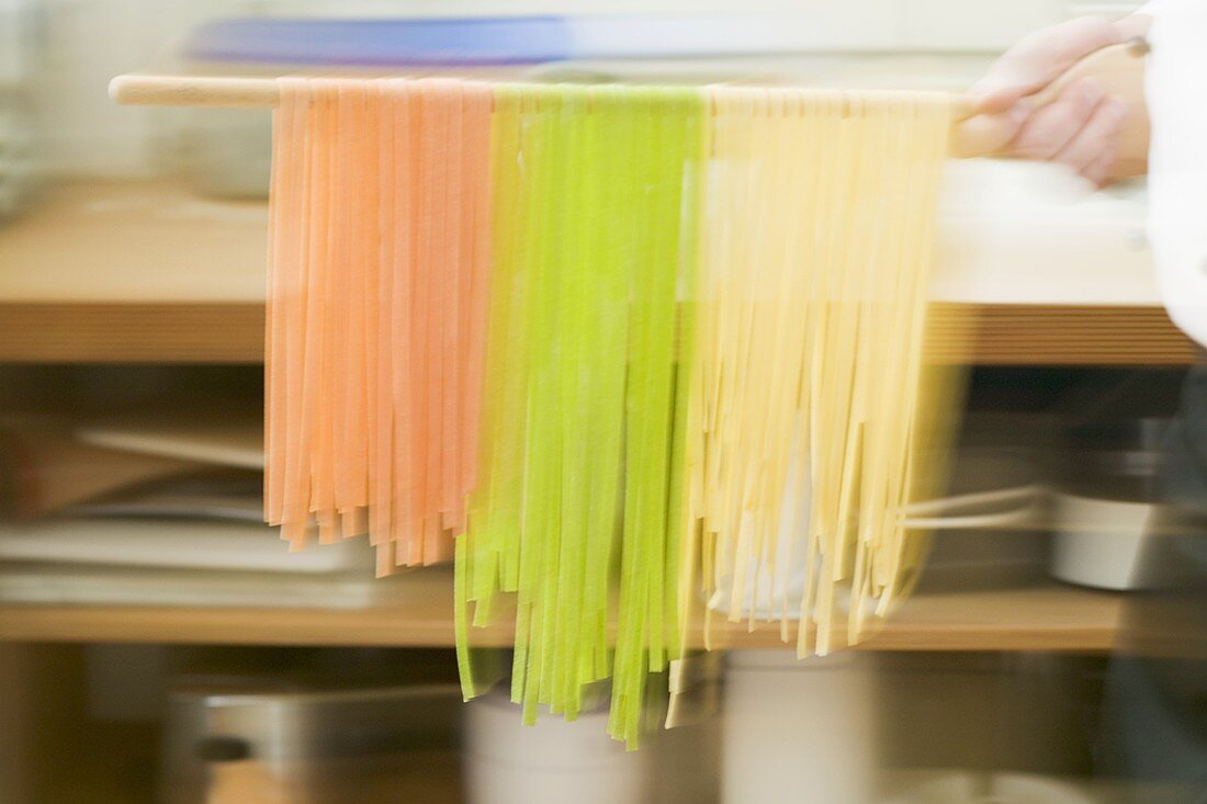Chef hurrying through kitchen with ribbon pasta on wooden spoon