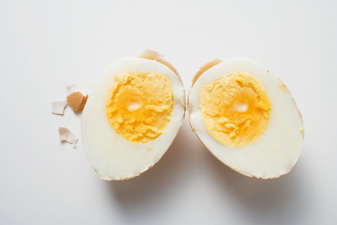 Hard-boiled egg with shell, halved