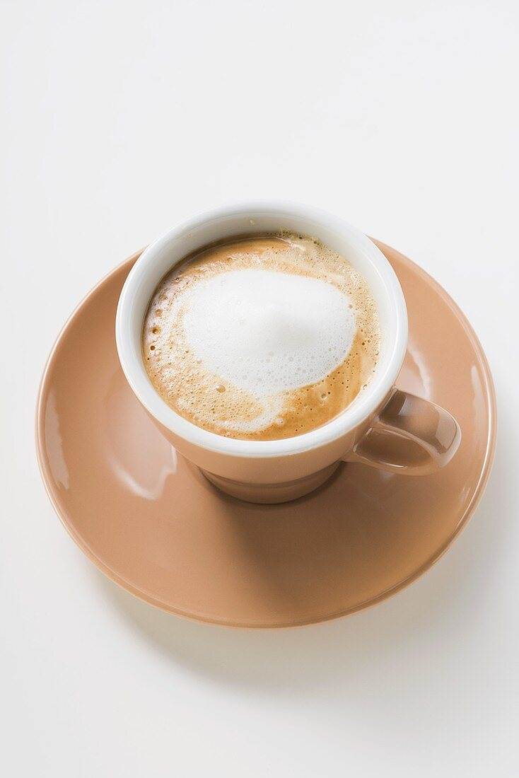Cup of espresso with milk froth (overhead view)
